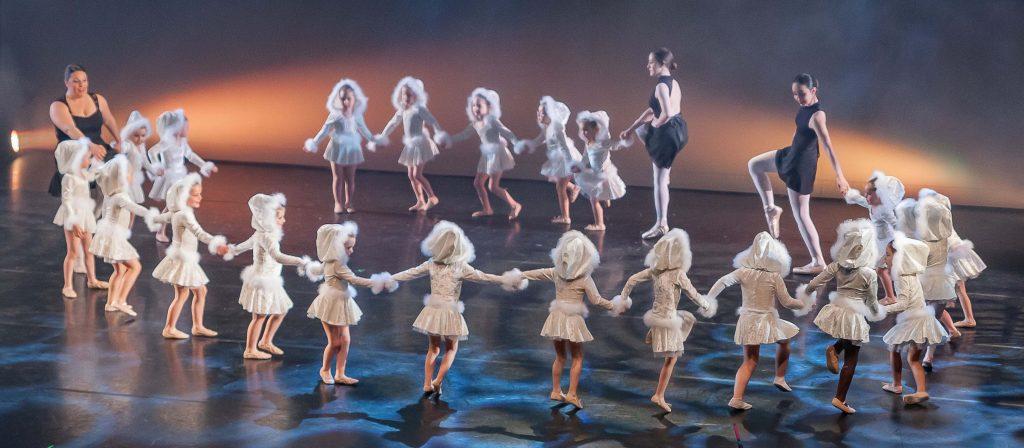 Un grand groupe d'enfants danse en rond.